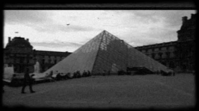 archival style black and white film footage of tourists visiting the louvre pyramid in paris. - newsreel stock videos & royalty-free footage