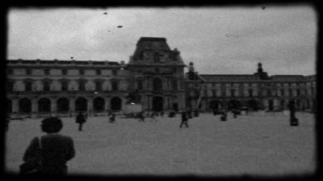 Archival style black and white film footage of tourists walking around the main courtyard of the Louvre Museum in Paris.