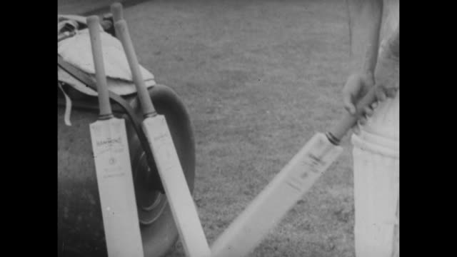 stockvideo's en b-roll-footage met archive film footage circa 1939 of gloucestershire and england cricketer walter hammond walking out to practice and having a net with his... - cricketveld