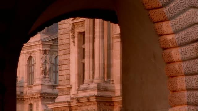 vidéos et rushes de archway looking onto louvre / paris, france - statue