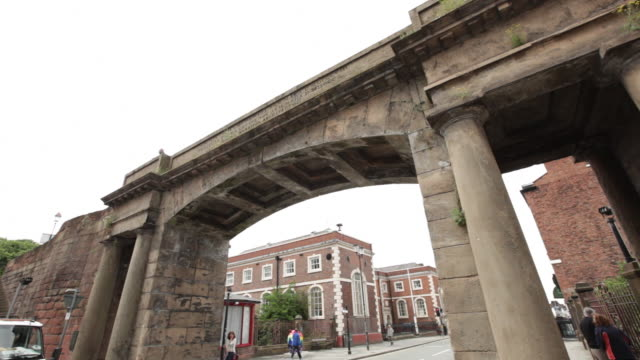 ms td pan archway over street with pedestrians and moving car / chester, england - 英国チェスター点の映像素材/bロール