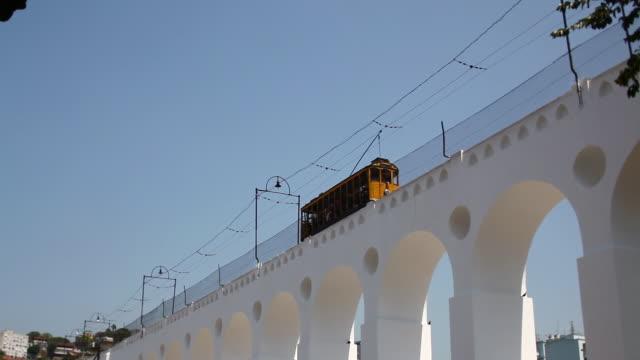 vídeos de stock, filmes e b-roll de ws arcos da lapa lapa's arches trolley passing by / rio de janeiro, brazil - low angle view