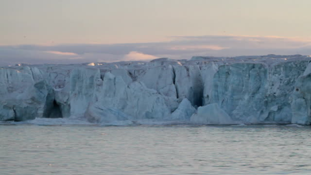 Arctic glacier calving at sunset, part one