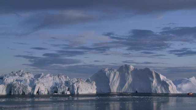 Arctic seascape with iceberg and small ship