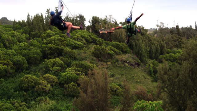 Areial shot revealing two people flying down a zipline