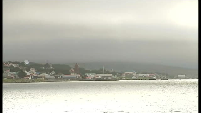 vidéos et rushes de argentina claim that britain is militarising falkland islands date unknown general view across bay of port stanley houses and cloudcovered hill in... - indication de direction