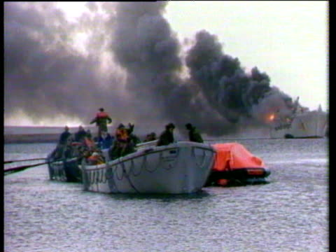 argentine attack at bluff cove, on the landing crafts sir galahad and sir tristram / soldiers climbing to shore from dingys and boats / smoke rising... - 1982 stock videos & royalty-free footage