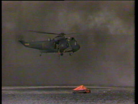 argentine attack at bluff cove, on the landing crafts sir galahad and sir tristram / chinook rescuing man in bright orange clothing / helicopters... - 1982 stock videos & royalty-free footage