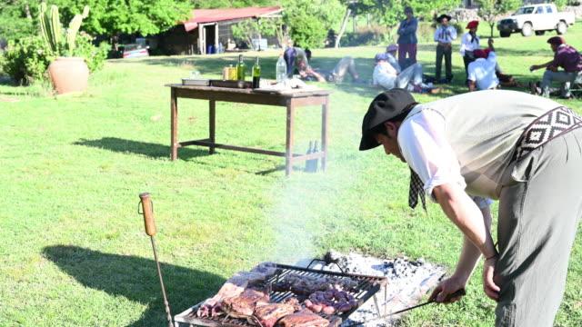 vídeos de stock e filmes b-roll de argentine gaucho asador arranging coals under grill - gaúcho