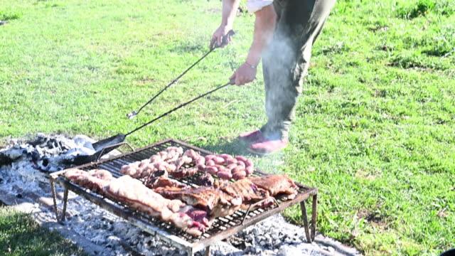 vídeos de stock e filmes b-roll de argentine gaucho grill master managing coals for asado - gaúcho
