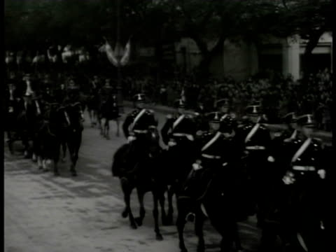 Argentineans watching man w/ hat at heart WS Argentine guards on horseback leading Argentine President Ramon Castillo in carriage waving to crowd WS...