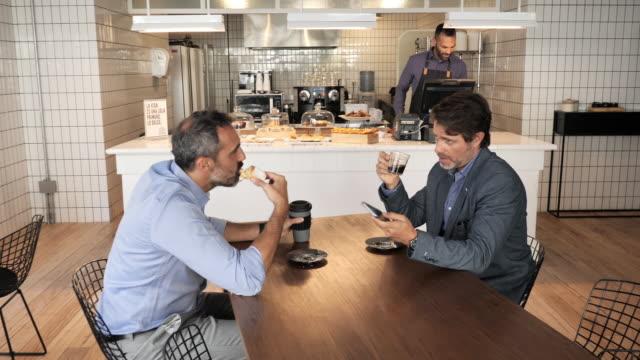 カフェに座ってコーヒーを飲むアルゼンチンのビジネスマン - カフェ点の映像素材/bロール