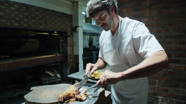 vídeos de stock, filmes e b-roll de chef argentino cortando carne de parrilla e transferindo-a para pratos - argentina