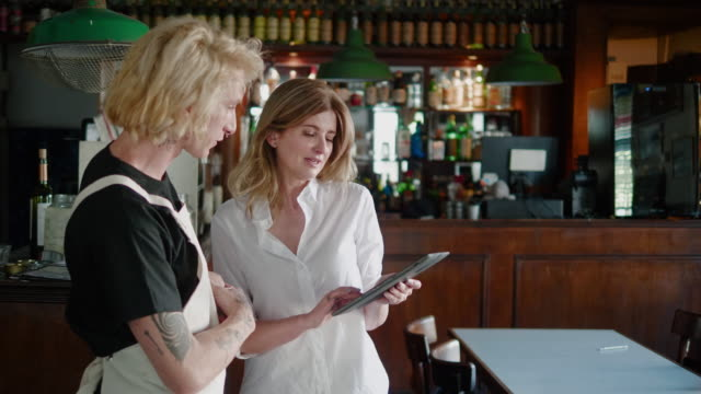 argentinian female restaurant manager speaking to the employee while using digital tablet - employee stock videos & royalty-free footage