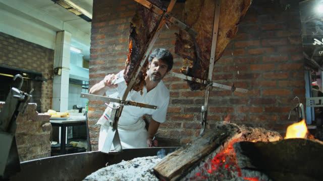 vídeos y material grabado en eventos de stock de chef argentino parrilla inspeccionando carne sobre fuego - argentina