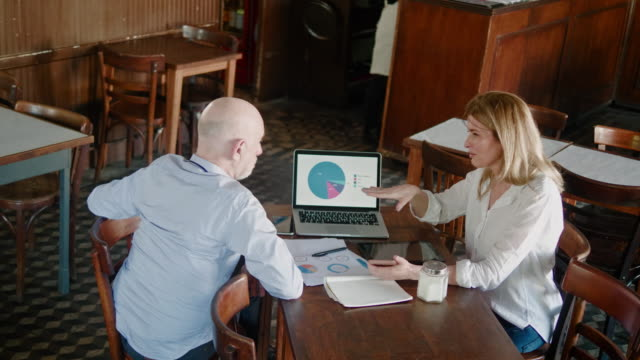 argentinian senior businessman and businesswoman having a meeting during lunch break in restaurant - pie chart stock videos & royalty-free footage