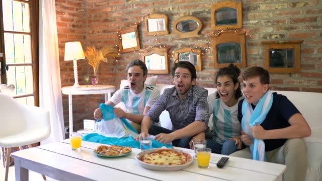argentinische fußballfans fröhlich, schreienessen pizza zum mitnehmen und fußball spielen - argentinische flagge stock-videos und b-roll-filmmaterial