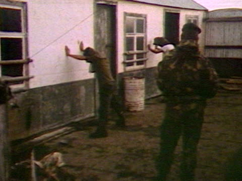 Argentinian troops are guarded by British soldiers during the Falklands crisis