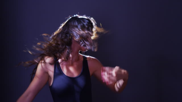 vídeos de stock e filmes b-roll de argentinian woman dancing and flipping hair in front of light - body de ginástica