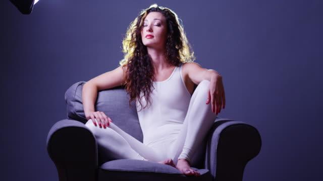 argentinian woman sitting in couch looking at light - gympingdräkt bildbanksvideor och videomaterial från bakom kulisserna