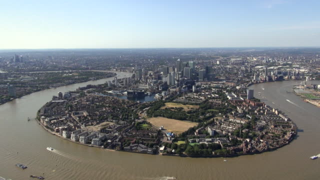 Arial panoramic view, panning across Isle of dogs and Canary Wharf in East London and including river Thames and O2 Arena