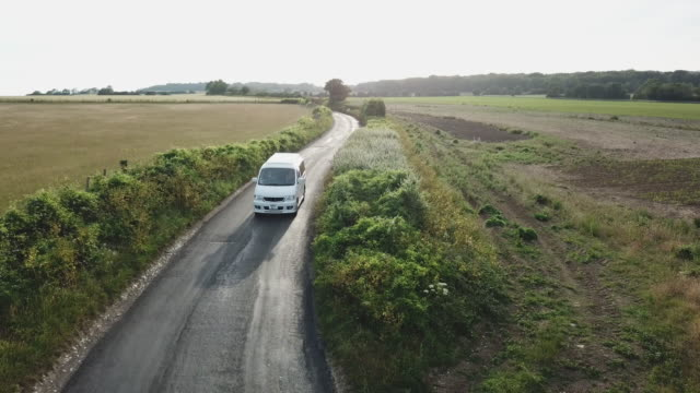 arial view from drone following campervan on scenic road trough fields at sunset - van stock videos & royalty-free footage