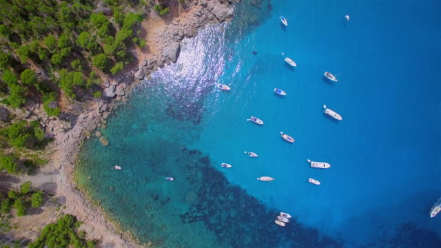 vídeos de stock e filmes b-roll de arial view of cala de ses ortigues on west coast near by andratx with relaxing sailboat on the water surface - spanish balearic island of majorca / spain - cordilheira montanha
