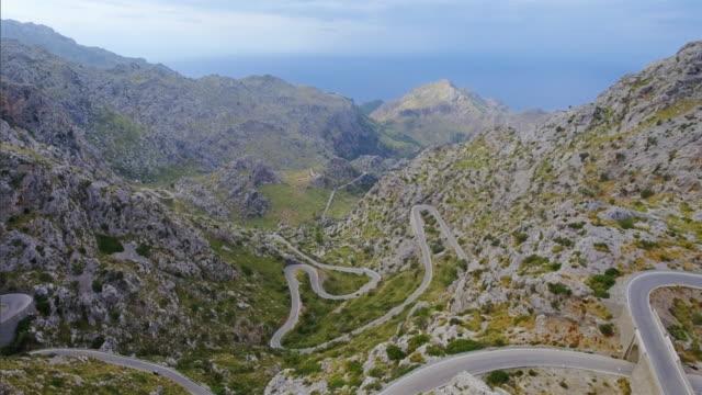 "arial view of hairpin turn "" nus de sa corbata "" to sa calobra - serra de tramuntana - coastal road stock videos & royalty-free footage"