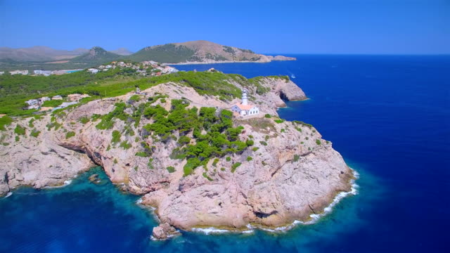 arial view of lighthouse - far de capdepera and rocky coastline near by cala rajada - northeastern coast on spanish balearic island of majorca / spain - balearic islands stock videos and b-roll footage