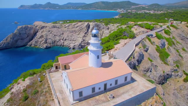 arial view of lighthouse - far de capdepera near by cala rajada and rocky coastline northeastern coast on spanish balearic island of majorca / spain - balearic islands stock videos and b-roll footage