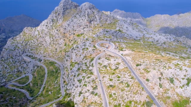 arial view of mountain range with hairpin turn nearby sa calobra - sierra de tramuntana / majorca - spain - majorca stock videos & royalty-free footage