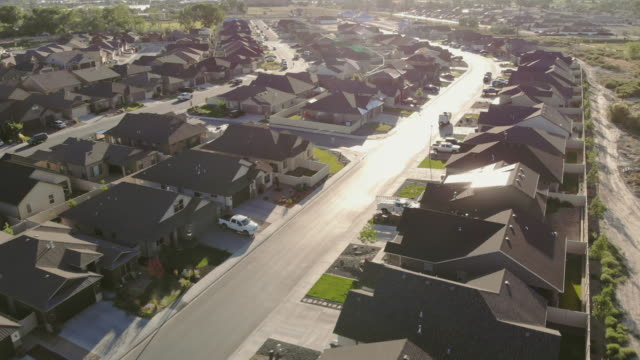 ariel view of neighborhood street lined with homes on a sunny summer day - tarmac stock videos & royalty-free footage