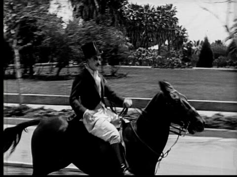 1924 b&w ms aristorcratic man riding horse/ man catching top hat as it falls off  - cravat stock videos and b-roll footage
