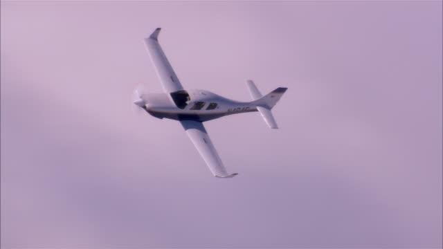 air to air, ha, usa, arizona, grand canyon, lancair legacy flying through white clouds - プロペラ機点の映像素材/bロール