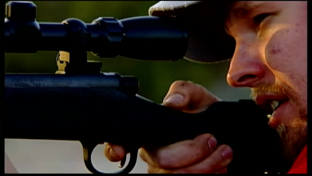debate over gun laws men clay pigeon shooting in desert silhouette of man firing gun man reloading rifle - tiro al piattello video stock e b–roll