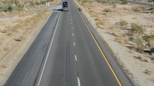 arizona highway interstate 10 through the sonora and mojave deserts, black semi-truck driving to camera on the highway, arizona desert, - interstate 10 stock videos & royalty-free footage