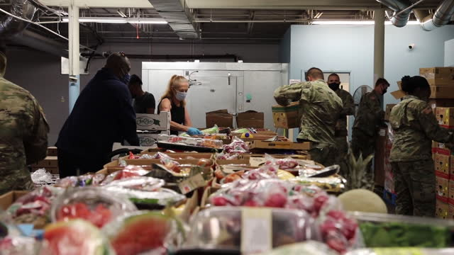 arizona national guard soldiers and airmen work with civilians distributing groceries to local citizens at a food bank in phoenix, mar. 08, 2021. - altruismo video stock e b–roll