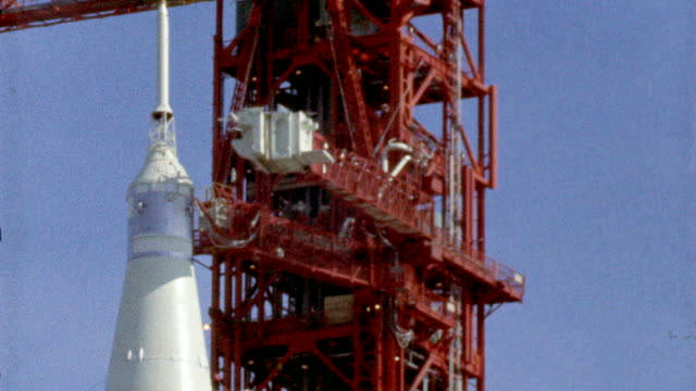 Arm braces pulling away from Apollo 11 rocket on launch pad / slow motion extreme close up of rocket lifting off