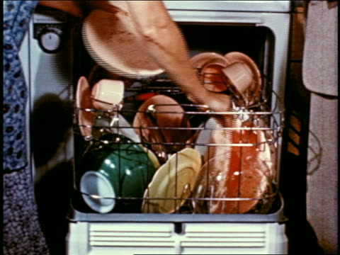 1955 arm of woman loading dishwasher with dirty dishes - lavastoviglie video stock e b–roll
