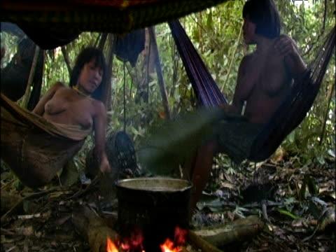 Armadillo cooks on fire in pot as Sanema women in hammocks fan fire with leaves Southern Venezuelan Rainforest