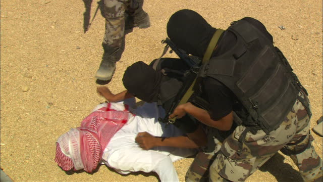 Armed and masked soldiers frisk a suspect, then quickly escort the suspect out of a training compound.