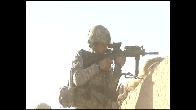 armed and uniformed soldier shoots practice rounds from rifle at army base in kabul during war in afghanistan - war or terrorism or military点の映像素材/bロール