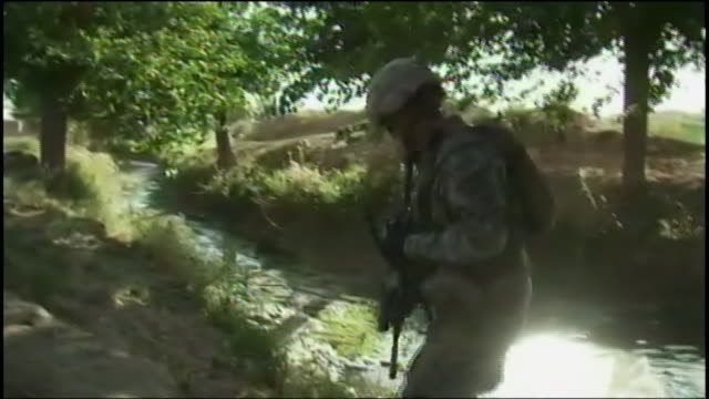 armed and uniformed soldiers march through brush during war in afghanistan. - war or terrorism or military点の映像素材/bロール
