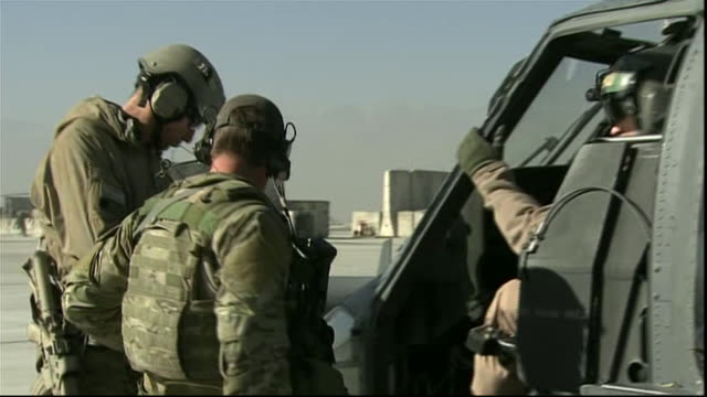 armed and uniformed us soldiers man helicopters at airbase during war in afghanistan - war or terrorism or military点の映像素材/bロール
