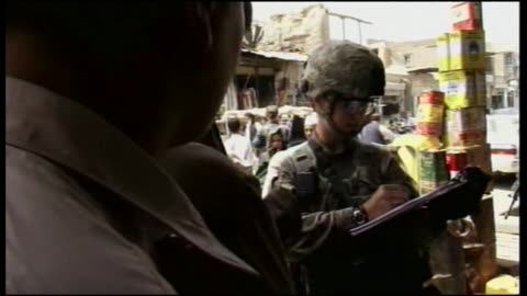 armed and uniformed us soldiers question locals at marketplace in afghanistan during wartime - war or terrorism or military stock videos & royalty-free footage