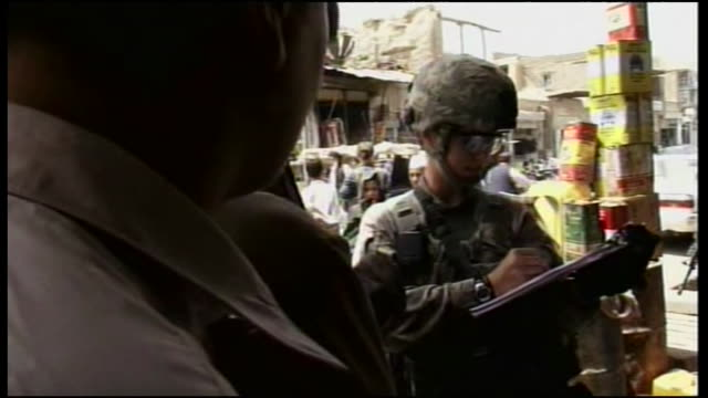 armed and uniformed us soldiers question locals at marketplace in afghanistan during wartime - afghan national army stock videos & royalty-free footage