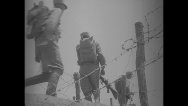 armed chinese nationalist soldiers march uphill and between barbed wire [note film has nitrate deterioration] - civil war stock videos & royalty-free footage