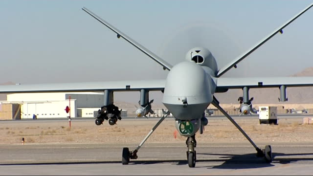 armed drones in afghanistan operating from raf base in uk lib helmand province camp bastion ext armed raf unmanned drone aircraft taxiing on runway... - 無人航空機点の映像素材/bロール