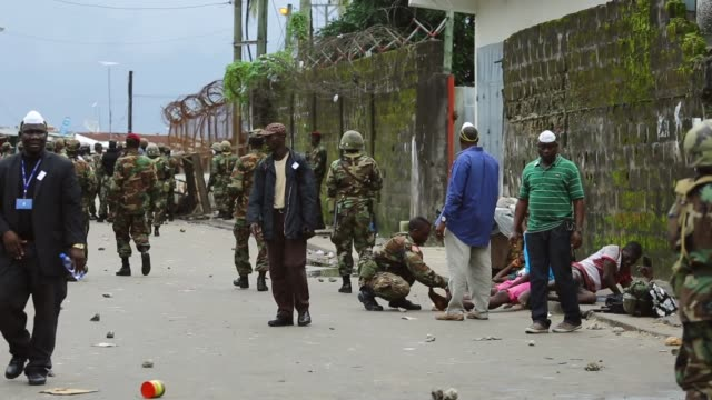 vídeos de stock, filmes e b-roll de armed forces of liberia attend to shakie kamara near the entrance to west point. a bullet from the melee apparently wounded his right leg after... - febre hemorrágica