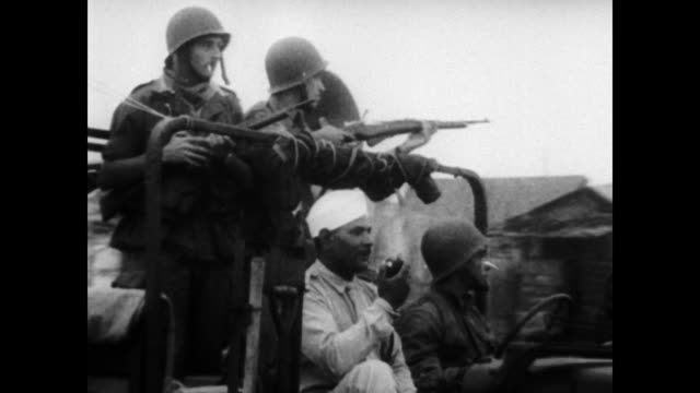 vídeos de stock e filmes b-roll de / armed french troops watch as moroccans carry wounded on stretchers / wounded loaded onto ambulance / large crowds of men seated on the floor /... - 1955